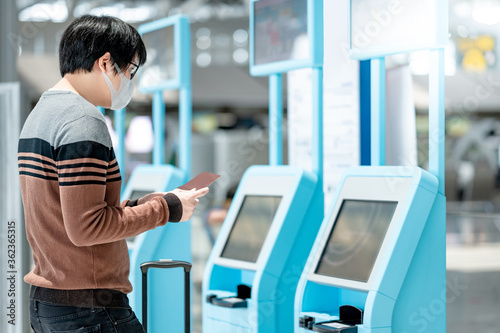 Photo Asian man tourist wearing face mask using self check-in kiosk in airport terminal