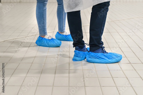 Stampa su Tela Close up on feet of unknown man and woman wearing overshoes - Blue medical shoe