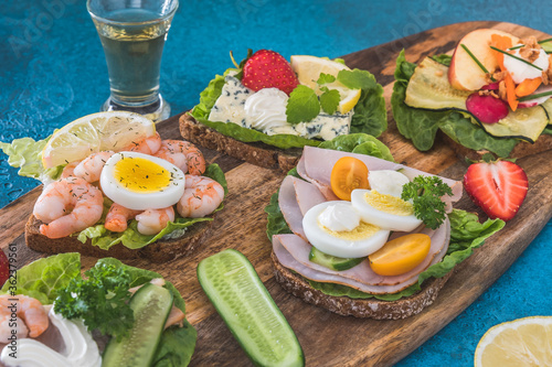 Photo Variety of danish open sandwiches on wooden boards and blue background, decorate