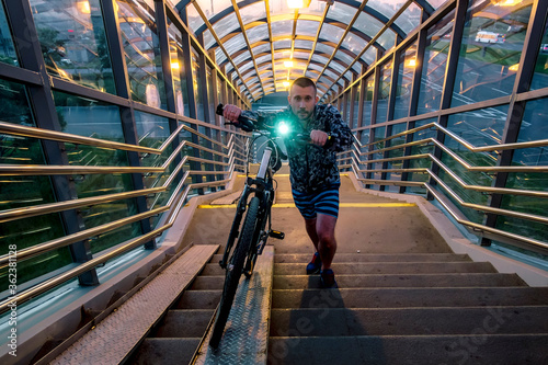 A man rolls a Bicycle in an overpass over the Pulkovo highway in Saint Petersburg #362381128