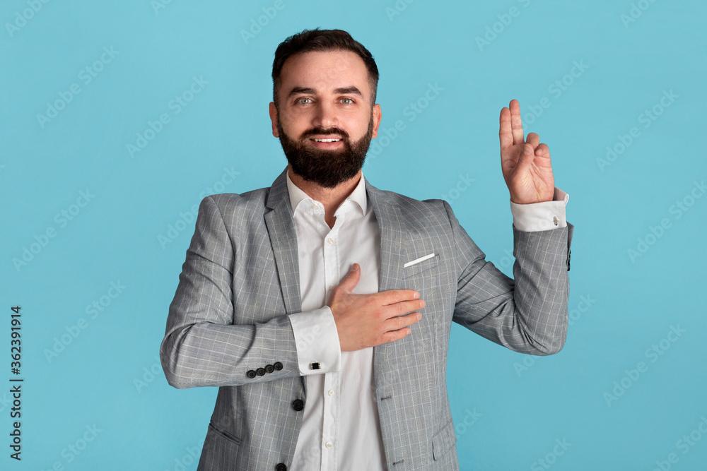 Fototapeta Portrait of millennial businessman taking oath on blue background