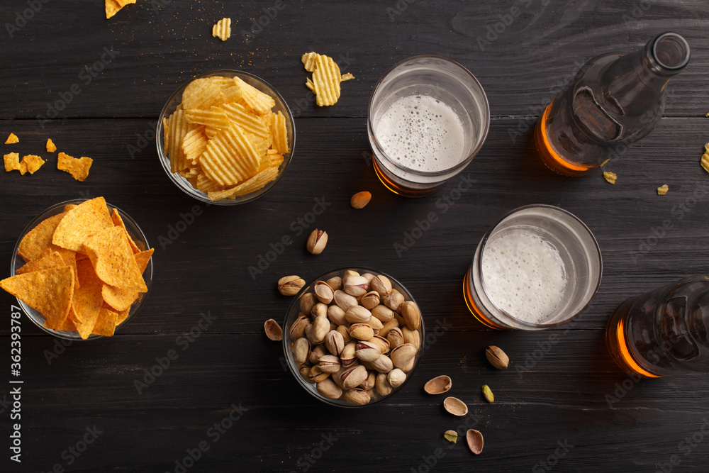 Fototapeta Beer in bottles and glasses, chips, nachos and pistachios in glass plates and scattered