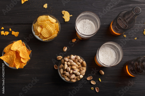 Fototapeta Beer in bottles and glasses, chips, nachos and pistachios in glass plates and scattered obraz