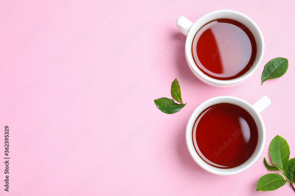 Fototapeta Cups of aromatic black tea and green leaves on pink background, flat lay. Space for text