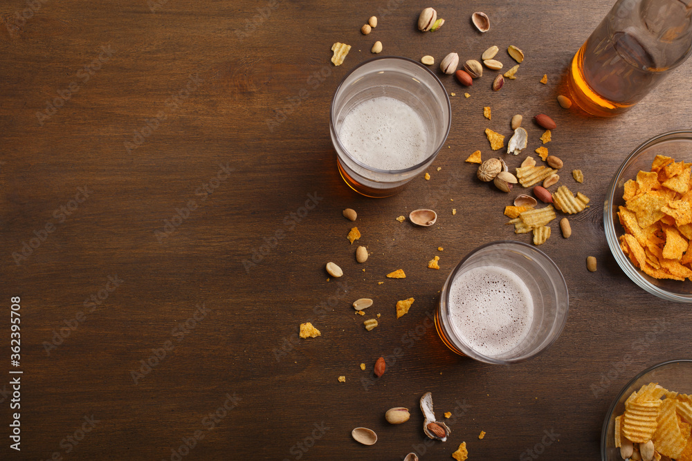 Fototapeta Beer and relaxation. Ale in bottles and glasses, chips, nuts and pistachios