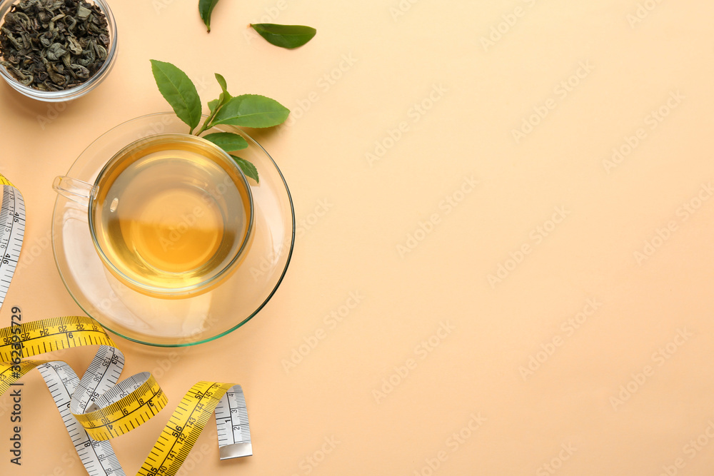 Fototapeta Flat lay composition with glass cup of diet herbal tea and measuring tape on orange background, space for text