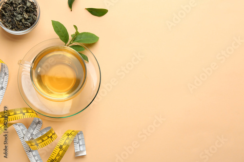 Fototapeta Flat lay composition with glass cup of diet herbal tea and measuring tape on orange background, space for text obraz