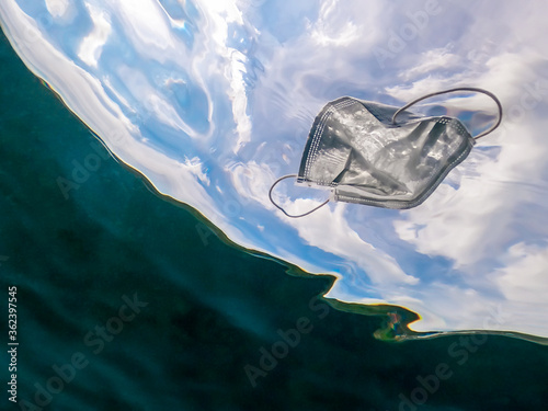 Fototapeta People throws out a medical face mask floating underwater on ocean water obraz