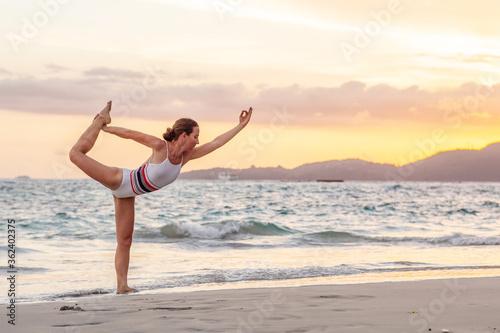 Cuadros en Lienzo Woman practices yoga at seashore
