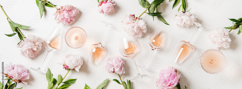 Fototapeta Rose wine variety layout. Flat-lay of rose wine in glasses and summer peony flowers over white background, top view. Summer drink for party, wine shop or wine tasting concept