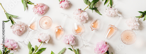 Rose wine variety layout. Flat-lay of rose wine in glasses and summer peony flowers over white background, top view. Summer drink for party, wine shop or wine tasting concept © sonyakamoz
