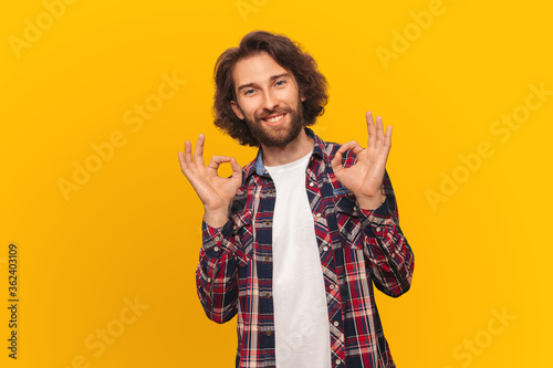 Valokuvatapetti Handsome man with long hair in a shirt smiling shows all is well yellow background