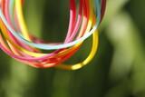Fototapeta Tęcza - Gumki wielokolorowe obręcze na zielonym tle