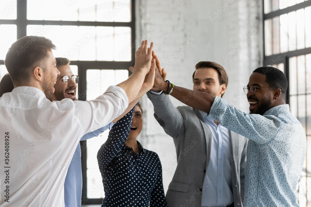 Fototapeta Multi racial millennial affiliates join hands giving high five celebrating common business success sales growth department promotion feels excited and motivated showing team spirit and synergy concept