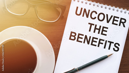 Uncover the Benefits - text written on notebook on wooden table with pen coffee Canvas Print
