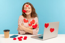 Charming Happy Young Woman With Kind Smile Sitting At Workplace Office, All Covered With Sticker Love Hearts, Embracing Herself, Enjoying Valentine's Day Greetings. Indoor Studio Shot, Isolated
