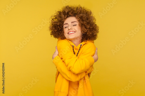 Valokuvatapetti I love myself! Portrait of self-satisfied egoistic curly-haired woman in urban style hoodie embracing herself and smiling with pleasure, feeling self-pride