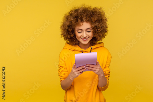 Photo Portrait of positive carefree student, curly-haired young woman in urban style hoodie reading funny joke, amusing story on paper notebook and laughing