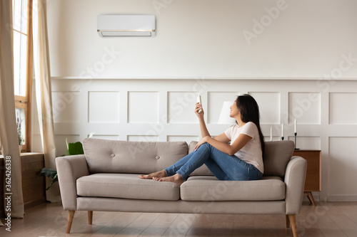 Photo Full length smiling young asian ethnic woman sitting on cozy sofa, turning on off air conditioner with remote controller, setting indoors temperature preference, managing cooling system at home