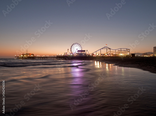 Dusk view of popular Santa Monica pier reflecting in pacific ocean water in Southern California. #362426506