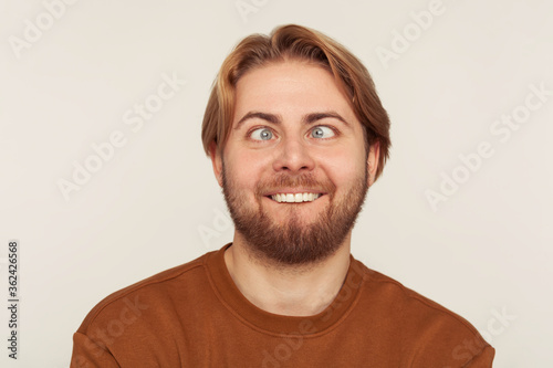 Closeup portrait of idiot, dumb bearded man looking cross-eyed with stupid smile, fooling around, making silly face, brainless comical expression Canvas Print