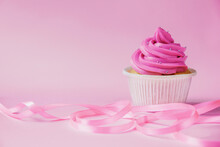 A Beautiful Cupcake With Bright Pink Cream And A Little Silver Decoration On A Pink Background. Pink Ribbon For Decor In The Foreground Lies In Waves. Festive Background With Free Space.