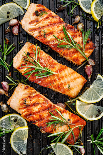 Fototapeta Grilled salmon fillets sprinkled with fresh herbs and lemon juice on a grill top view obraz