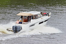 Beautiful Contemporary White Cabin Powerboat With Double Powerful Outboard Motor Fast Floating On Water With Splashes, Rear Side Top View On Summer Day, Speed Motor Boat Active Recreation, Watersports