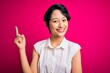 Leinwanddruck Bild - Young beautiful asian girl wearing casual summer shirt standing over isolated pink background with a big smile on face, pointing with hand and finger to the side looking at the camera.