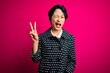 Leinwanddruck Bild - Young beautiful asian girl wearing casual jacket standing over isolated pink background smiling with happy face winking at the camera doing victory sign with fingers. Number two.
