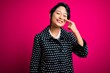 Leinwanddruck Bild - Young beautiful asian girl wearing casual jacket standing over isolated pink background Pointing with hand finger to face and nose, smiling cheerful. Beauty concept