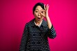 canvas print picture - Young beautiful asian girl wearing casual jacket standing over isolated pink background doing ok gesture shocked with surprised face, eye looking through fingers. Unbelieving expression.