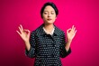 Leinwanddruck Bild - Young beautiful asian girl wearing casual jacket standing over isolated pink background relaxed and smiling with eyes closed doing meditation gesture with fingers. Yoga concept.