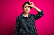 canvas print picture - Young beautiful asian girl wearing casual jacket standing over isolated pink background making fun of people with fingers on forehead doing loser gesture mocking and insulting.