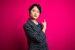 Leinwanddruck Bild - Young beautiful asian girl wearing casual jacket standing over isolated pink background Pointing with hand finger to the side showing advertisement, serious and calm face