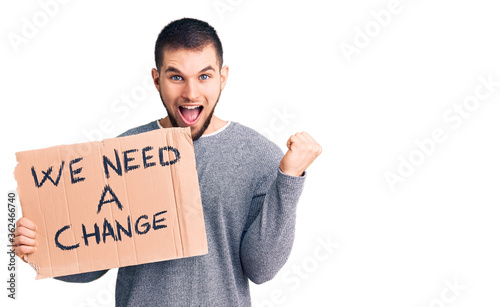 Obraz na płótnie Young handsome man holding we need a change banner screaming proud, celebrating