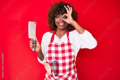 Young african american woman wearing cook apron holding knife smiling happy doin Fototapeta