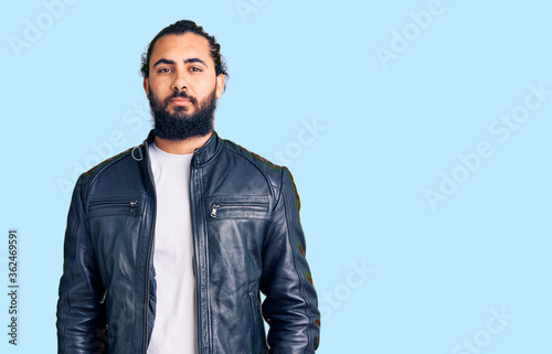 Obraz na plátně Young arab man wearing casual leather jacket relaxed with serious expression on face