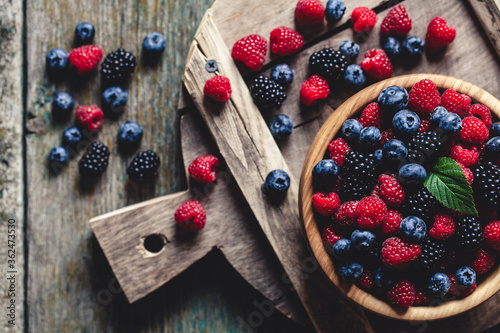 Photo blueberries and raspberries, blackberry in a wooden bowl on old wood background