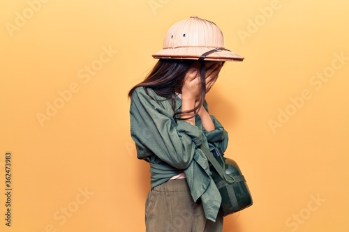 Fotografie, Obraz Beautiful child girl wearing explorer hat with sad expression covering face with hands while crying