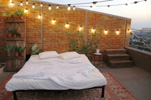 Open-air Rooftop Bed Next To Brick Wall