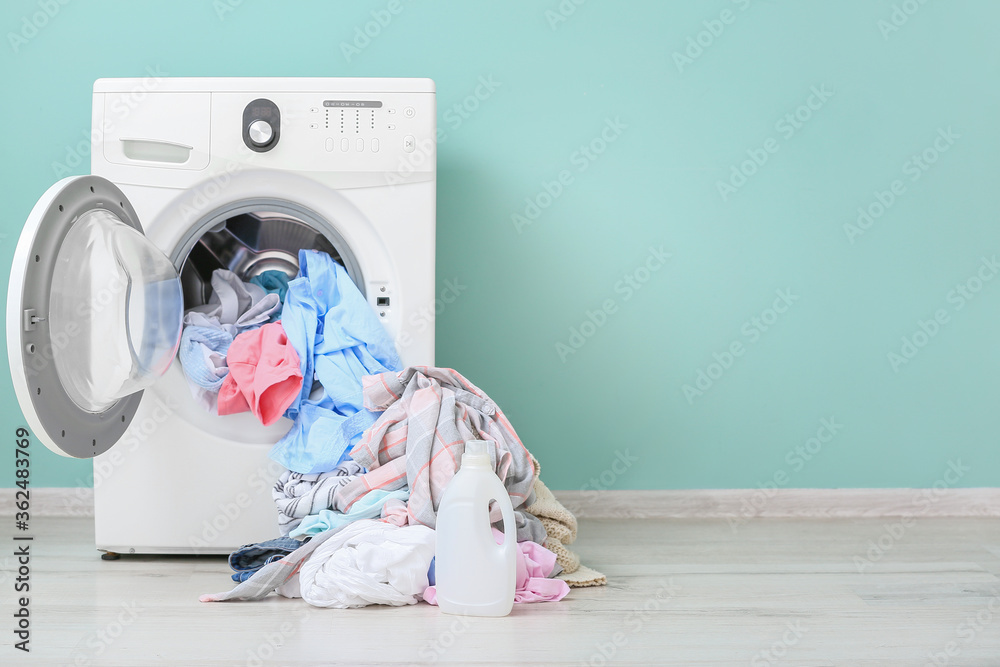 Fototapeta Washing machine with dirty clothes and detergent in home laundry room