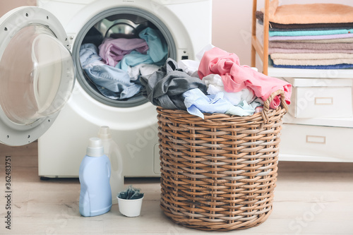 Foto Washing machine and basket with dirty clothes in home laundry room