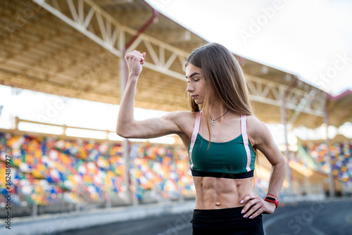 Fotografie, Obraz Young sportive woman making morning exercises outdoors on the stadium