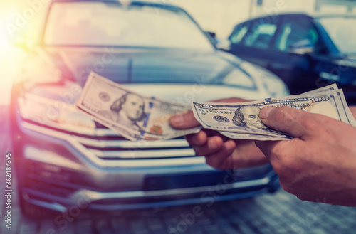 Obraz dealer make agreement to buy a new car, man holding dollar - fototapety do salonu