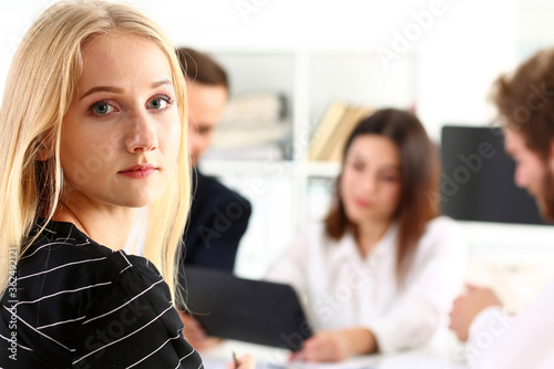 Fototapeta Beautiful smiling cheerful girl at workplace look in camera with colleagues group in background. White collar worker at workspace, job offer, modern lifestyle, client visit, profession train concept obraz na płótnie