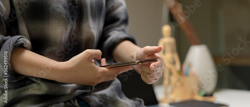 Fényképezés Female worker sitting on worktable and using smartphone to contact customer in o