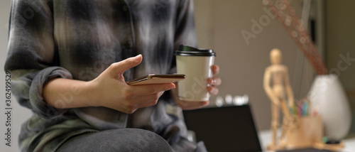 Female worker sitting on worktable and using smartphone while holding coffee in Tapéta, Fotótapéta