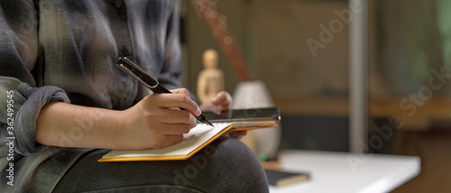 Fényképezés Female worker sitting on worktable and taking note on blank schedule book while