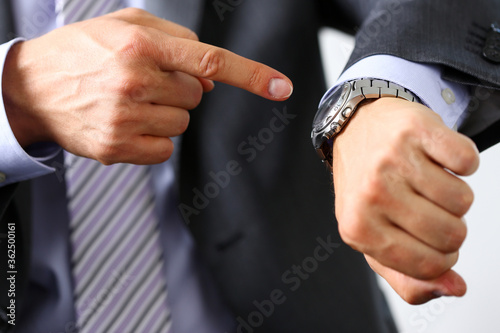 Fototapeta Man in suit and tie check out time at silver wristwatch closeup
